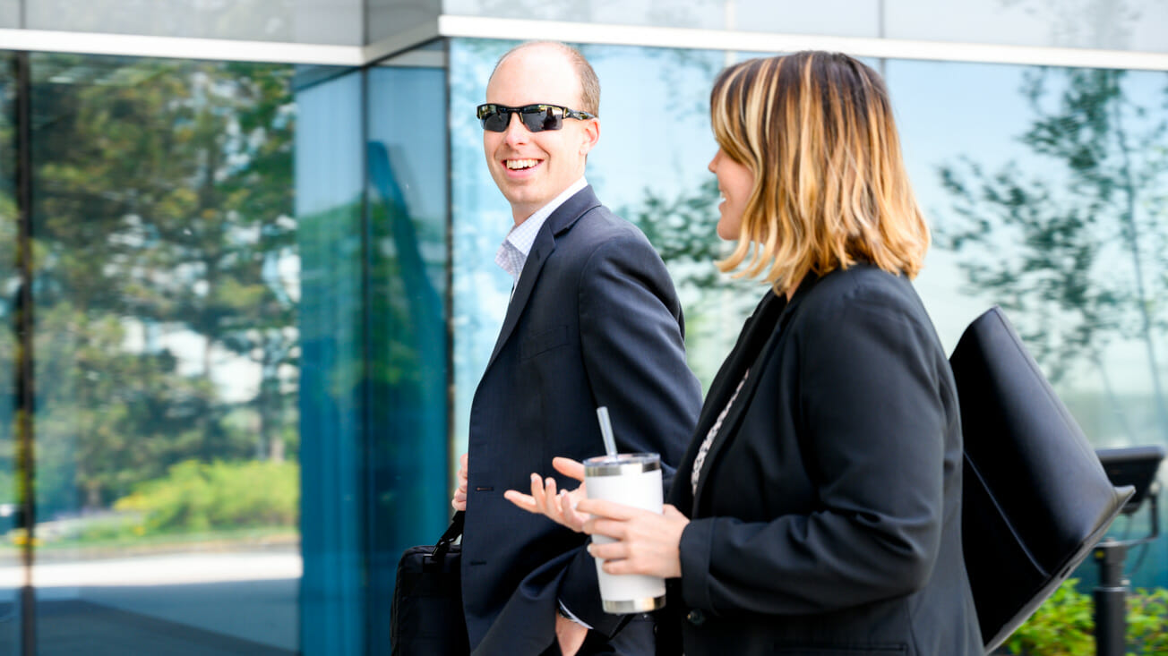 Two employees talk while walking outside
