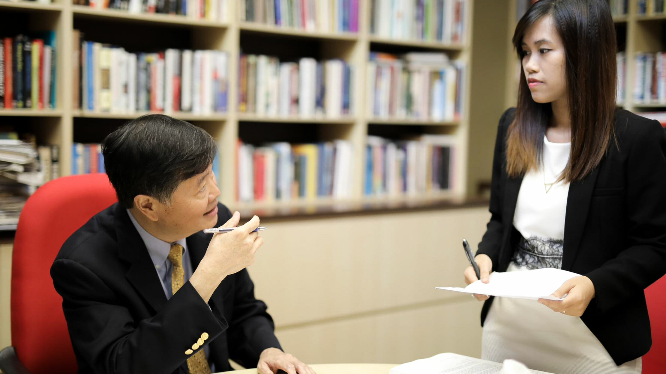 Man sitting at table while standing woman holds papers
