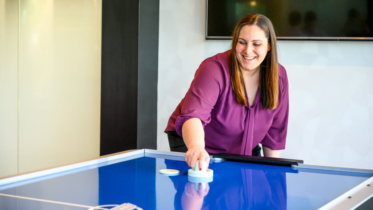 Woman plays air hockey in office game room